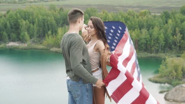 Happy couple holding the American flag in nature. Independence Day, lifestyle, travel concept Happy couple holding the American flag in nature. Independence Day, lifestyle, travel concept family 4th of july stock videos & royalty-free footage