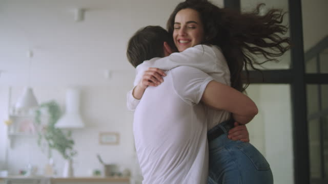 Happy couple hugging at new home. Love couple spinning around Happy couple hugging at new home. Love couple spinning around in slow motion. Close up of romantic man hugging woman. Young family enjoy new apartment hug stock videos & royalty-free footage