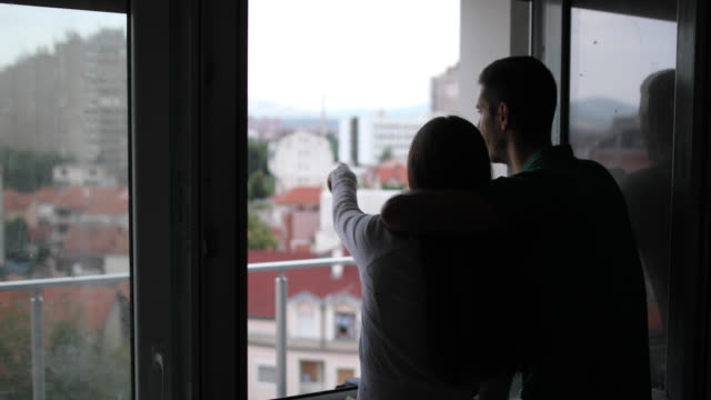Happy couple hugging while looking trough the window of their new flat video