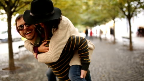 Happy couple in autumn Two people having fun in autumn outdoors,piggyback riding enjoyment stock videos & royalty-free footage