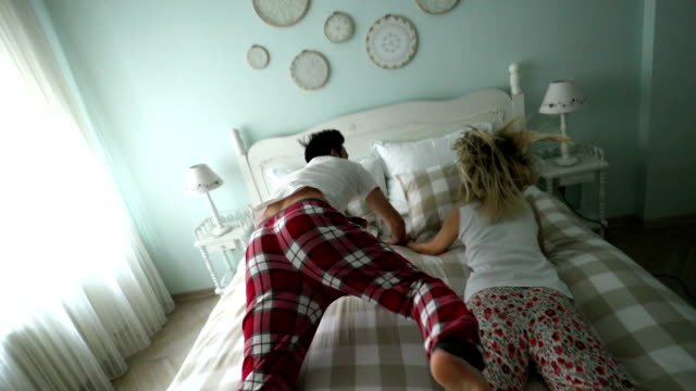 happy couple in love jumping on bed together - pajamas stock videos & royalty-free footage