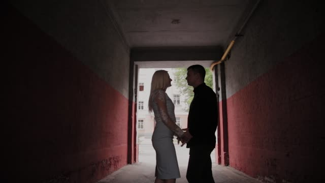 Happy couple in love standing under the arch at home and holding hands