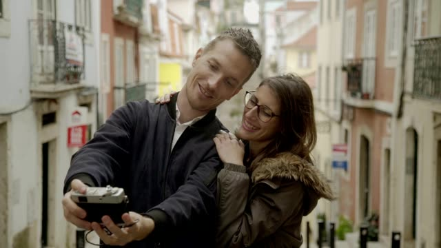 happy couple in love taking selfie with old vintage camera. - brunette woman eyeglasses kiss man video stock e b–roll