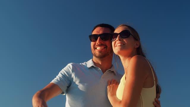 coppia felice in occhiali da sole in cerca di tariffa - fare video stock e b–roll