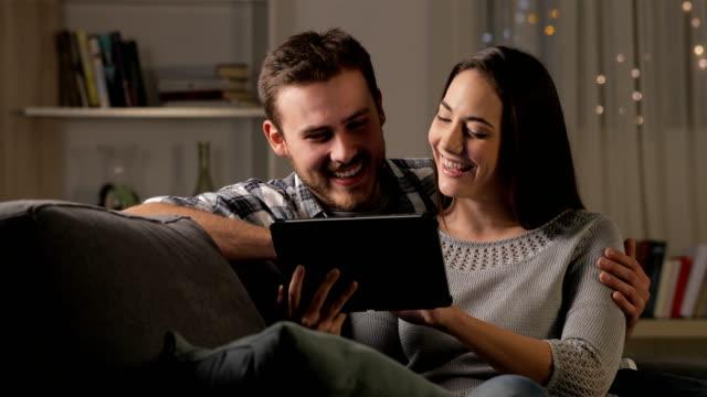 vídeos y material grabado en eventos de stock de pareja feliz en la noche viendo el contenido de la tableta - shopping online