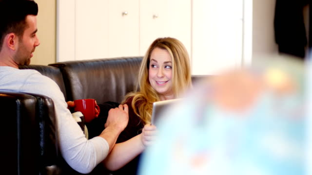 Happy couple interacting with each other on sofa video