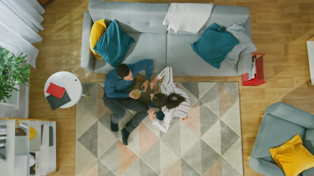 happy couple is sitting on a floor and talking. girl brings a cup of coffee to a young man. cozy living room with modern interior with sofa, chair, table, shelf, plants and wooden floor. top view with zoom in. - moquette video stock e b–roll