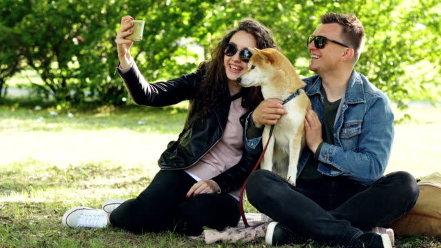 vídeos de stock e filmes b-roll de happy couple is taking selfie with their dog using smartphone sitting on grass in the park, people are posing, talking and petting shiba inu puppy. - fotografar
