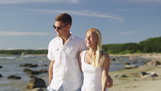 Happy Couple is Walking on Beach in Sunny Day. Slow motion 60 FPS. video