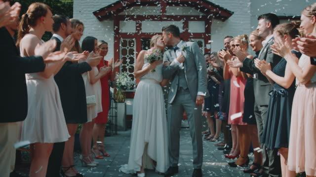 happy couple kissing amidst guests outside church - video di matrimonio video stock e b–roll