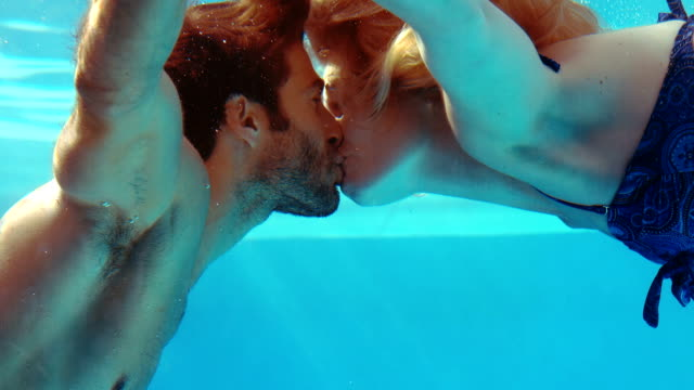Happy couple kissing underwater Happy couple kissing underwater in the pool kissing stock videos & royalty-free footage