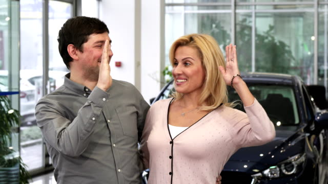 Happy couple laughing high fiving after buying a new car at the dealership video