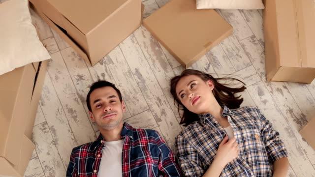 Couple heureux se trouve sur plancher avec boîtes déballés. - Vidéo