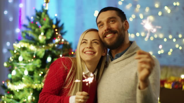 Happy Couple Light Sparklers and Smile. In the Background Christmas Tree and Room Decorated with Lights. video