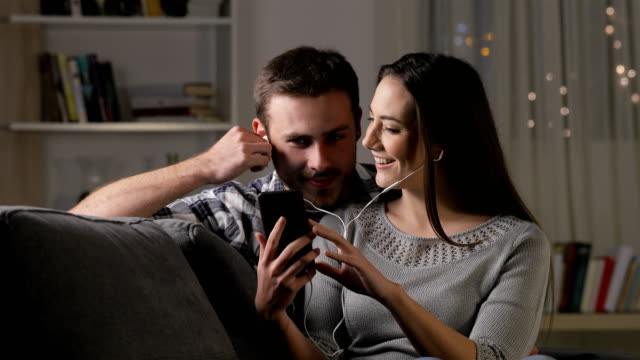 Happy couple listening to music sharing earphones