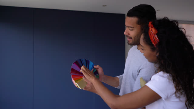 Happy couple looking at a color swatch and the wall they want to paint at their new home Happy couple looking at a color swatch and the wall they want to paint at their new home - Lifestyles choosing stock videos & royalty-free footage
