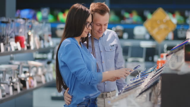Happy couple looking at a new digital camera at an electronics shop Happy couple looking at a new digital camera at an electronics shop. electronics store stock videos & royalty-free footage