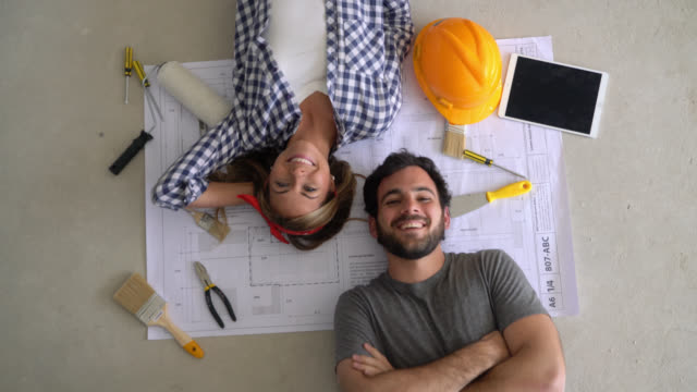 Happy couple lying down on floor on top of a blueprint and tools ready for a DIY project smiling at camera Happy couple lying down on floor on top of a blueprint and tools ready for a DIY project smiling at camera - DIY concepts renovation stock videos & royalty-free footage