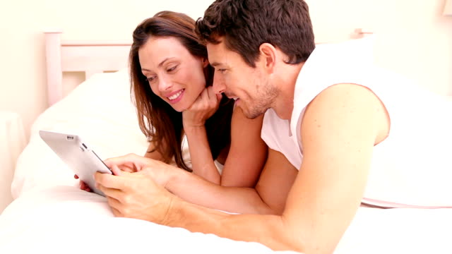 happy couple lying on bed using tablet - 30 39 år bildbanksvideor och videomaterial från bakom kulisserna