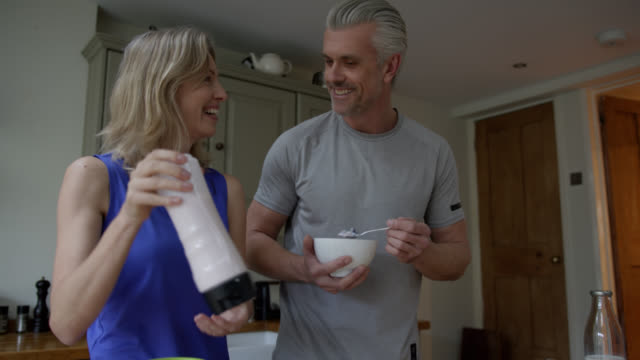 Happy couple making post workout smoothie at home using a blender video