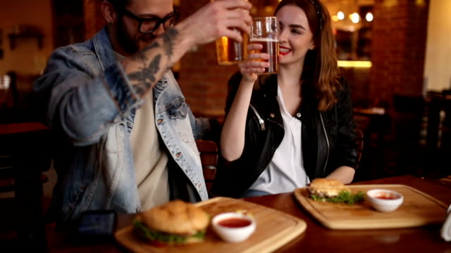 happy couple making toast in a pub - date night stock videos & royalty-free footage