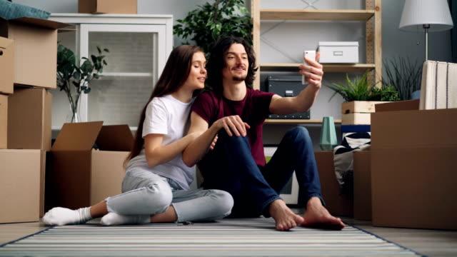 glückliches paar, das nach dem umzug videoanrufe mit dem smartphone macht und lächelt - schlüssel videos stock-videos und b-roll-filmmaterial
