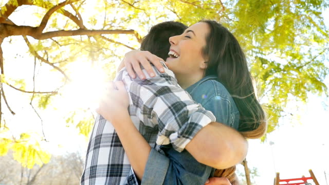 Happy couple meeting and hugging in a park Happy couple meeting walk each other and hugging in a park face to face stock videos & royalty-free footage