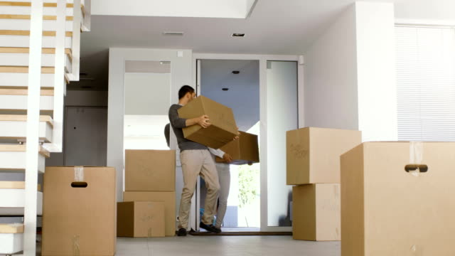 Happy Couple Move Boxes with Stuff into Their New Bright and Modern House. A lot of Boxes Already Stand in the Room. Happy Couple Move Boxes with Stuff into Their New Bright and Modern House. A lot of Boxes Already Stand in the Room. house rental stock videos & royalty-free footage
