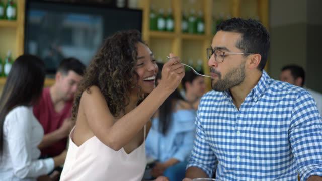 happy couple on a date and partner feeding her boyfriend smiling - incontro romantico video stock e b–roll