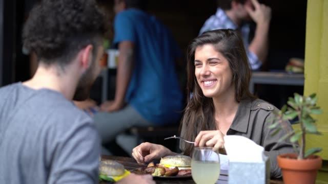 coppia felice ad un appuntamento in un ristorante che pranza parlando e sorridendo - argentina america del sud video stock e b–roll