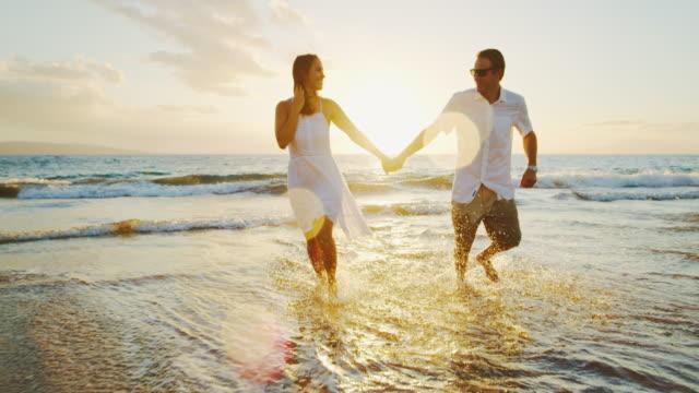 lyckliga paret på stranden vid solnedgången - aktivitet bildbanksvideor och videomaterial från bakom kulisserna