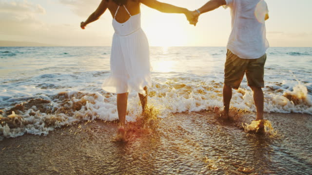 happy couple on the beach at sunset - exotic stock videos & royalty-free footage