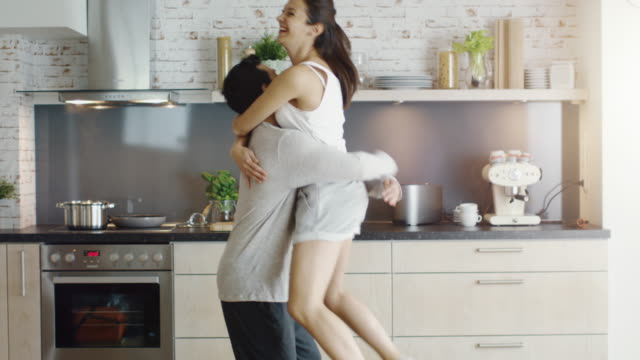 Happy Couple on the Kitchen. Girl Jumps into Guy's Arms. video