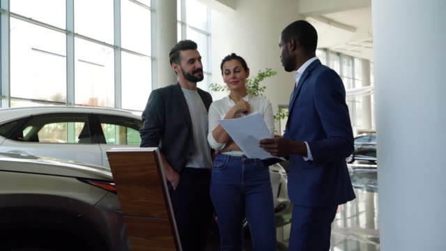 Happy couple paying attention to black salesman talking about the properties of a car at a dealership Happy couple paying attention to black salesman talking about the properties of a car at a dealership - Lifestyles car salesperson stock videos & royalty-free footage