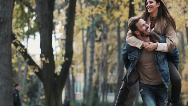 Happy couple piggybacking and having fun in the park. video