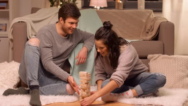vídeos de stock e filmes b-roll de happy couple playing block stacking game at home - hygge