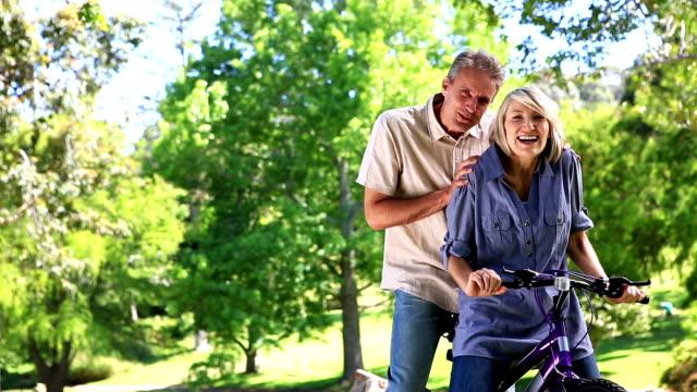 szczęśliwa para pozujących z rower w parku - 50 54 lata filmów i materiałów b-roll