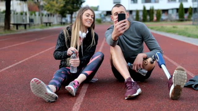 lyckligt par avkopplande efter träningspass - fysiskt funktionshinder bildbanksvideor och videomaterial från bakom kulisserna