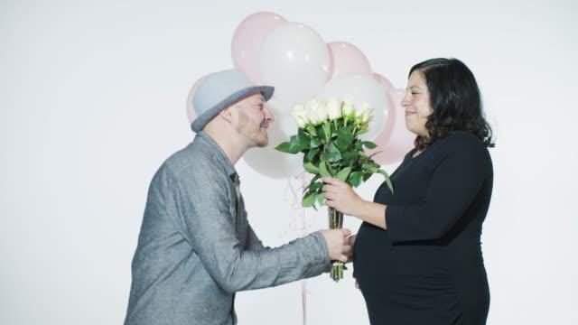 vidéos et rushes de heureux couple homme romance don de white rose ballons roses blanches embrasser le ventre de femme enceinte odeur fleurs - fête de naissance
