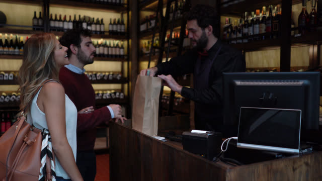 Happy couple saying goodbye to friendly sommelier packing a wine bottle in a paper bag at a wine cellar