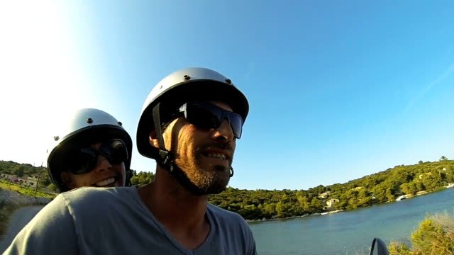 Happy couple scooter adventure on island holiday Slow Mo video