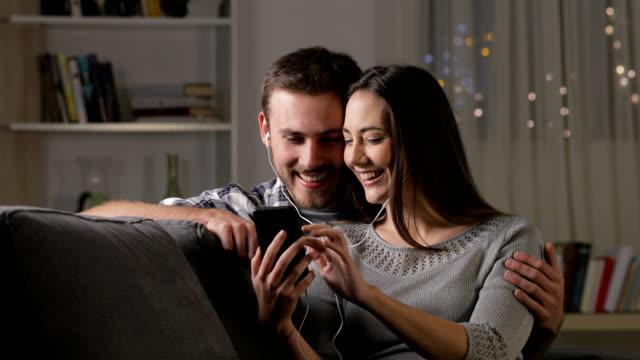 lyckliga par delar hörlurar titta på videor - videor med headphones bildbanksvideor och videomaterial från bakom kulisserna