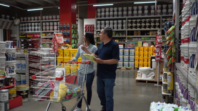 Happy couple shopping at a home improvement store following a list on a clipboard and smiling