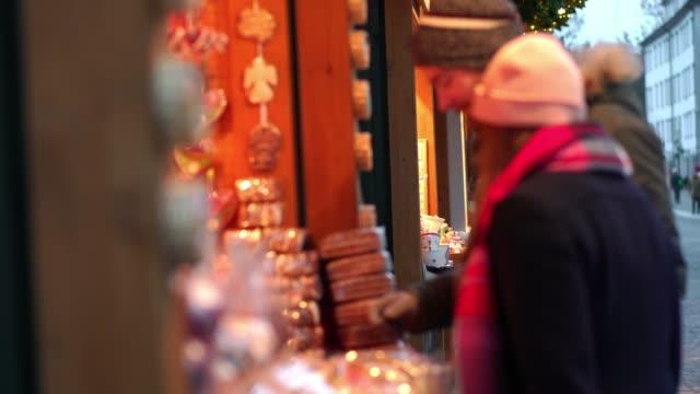 glückliches paar einkaufsmöglichkeiten für zu hause meade geschenke am weihnachtsmarkt - weihnachtsmarkt stock-videos und b-roll-filmmaterial