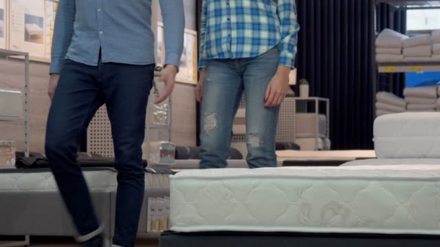 Happy couple shopping for new bed at furniture store Happy couple shopping for new bed at furniture store. Attractive housewife choosing orthopedic mattress with her husband at furnishings shop. Love, couples, relax, home concept furniture stock videos & royalty-free footage