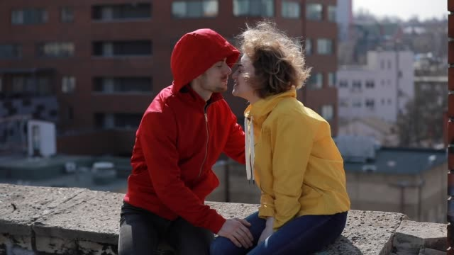 Happy couple sitting and kisses on the roof video