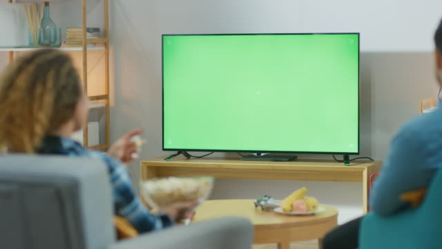 happy couple sitting at home in the living room watching green chroma key screen tv, relaxing on a couch. couple room watching sports match, news, show or a movie. - oglądać filmów i materiałów b-roll