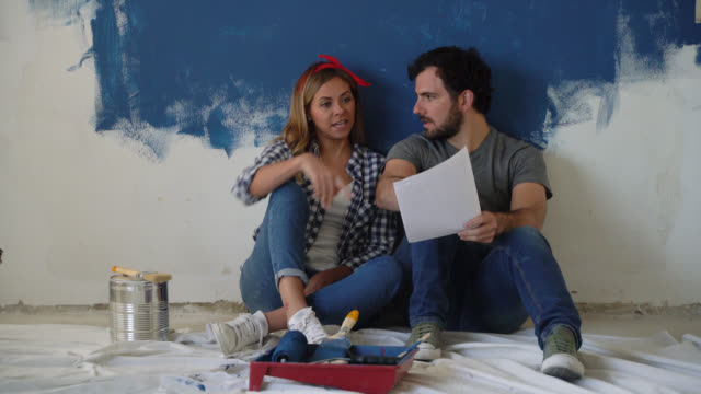 vídeos de stock e filmes b-roll de happy couple sitting on the floor looking at a design on paper during a home renovation - bricolage