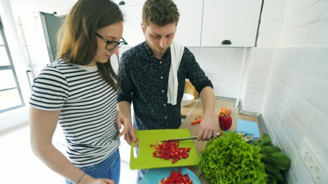 幸せなカップルは、一緒にキッチンで時間を過ごします。 - ローフード点の映像素材/bロール