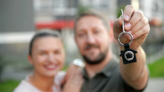 vídeos de stock e filmes b-roll de happy couple standing in front of a new home. good mood - buy a house key